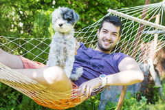 Young handsome man Relaxing In Hammock with his white dog Stock Photo