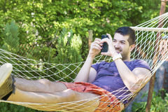 Young handsome man Relaxing In Hammock and playing with his phone Royalty Free Stock Photography