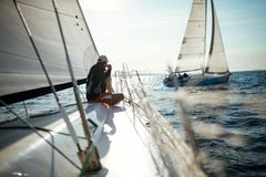 Young handsome man relaxing on his sailboat Stock Photography