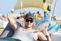 Young handsome man relaxing on a sunbed and looking the blue sea Royalty Free Stock Photos