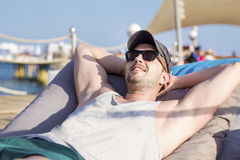 Young handsome man relaxing on a sunbed and looking the blue sea Royalty Free Stock Images