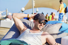 Young handsome man relaxing on a sunbed and looking the blue sea Royalty Free Stock Image