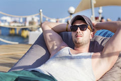Young handsome man relaxing on a sunbed and looking the blue sea. Young beautiful man relaxing on the beach ,looking the sea royalty free stock photos