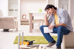 The young handsome man repairing chair at home stock images