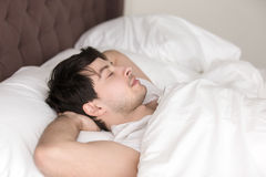 Young handsome man resting alone in bed with eyes closed. Relaxed guy lying up in comfortable cozy bed wearing white t-shirt, sleeping or napping with eyes stock photo