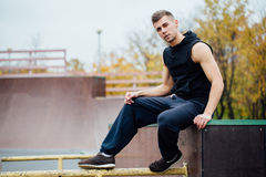 Young handsome man resting on a skateboard park ramp. Royalty Free Stock Photography