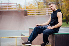 Young handsome man resting on a skateboard park ramp. Posing Royalty Free Stock Photo