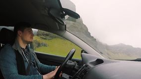 Young handsome man riding the car through the beautiful road in the mountains. Male driver talking with people, friends. Young handsome man riding the car stock video