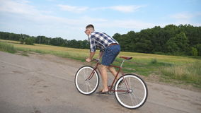 Young handsome man riding at vintage bicycle in the country road. Sporty guy cycling at the rural trail. Male cyclist stock video footage