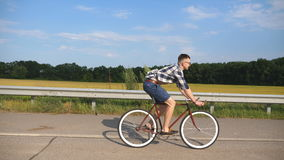 Young handsome man riding at vintage bicycle in the country road. Sporty guy cycling at the track. Male cyclist riding. Fixed gear bike at highway. Healthy Royalty Free Stock Photos