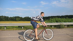 Young handsome man riding at vintage bicycle in the country road. Sporty guy cycling at the track. Male cyclist riding. Fixed gear bike at highway. Healthy Stock Images