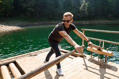 Young handsome man rowing oars in Carpathian mountains lake. Young handsome man in sunglasses rowing oars in Carpathian mountains lake. Copy space Royalty Free Stock Photos