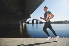 Young handsome man running along the embankment Royalty Free Stock Photo