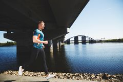 Young handsome man running along the embankment Royalty Free Stock Image