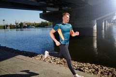 Young handsome man running along the embankment Stock Photography