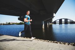 Young handsome man running along the embankment Stock Photos
