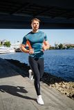 Young handsome man running along the embankment Royalty Free Stock Photography