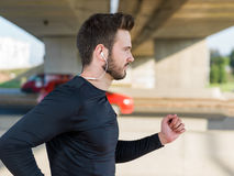 Young handsome man running along street and highway Stock Photography