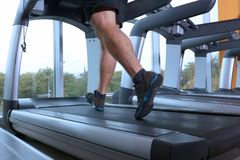 Young handsome man running on treadmill. In gym Stock Photography