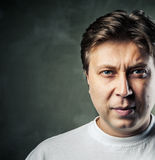 Young handsome man with serious expression on dark Royalty Free Stock Image