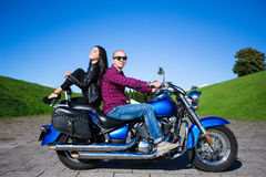 Young handsome man and sexy woman sitting on retro motorcycle Royalty Free Stock Photos