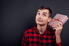 Young handsome man shakes a gift box to find out what`s in it. Young curious man shakes a gift box to find out what`s in it Royalty Free Stock Photo