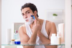 The young handsome man shaving early in the morning at home. Young handsome man shaving early in the morning at home Royalty Free Stock Photo