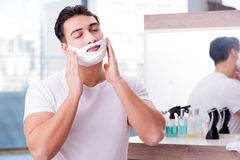 The young handsome man shaving in the morning Stock Images