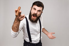 Young handsome man shouting holding cigar over white background. stock images
