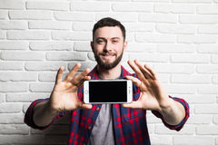 Young handsome man show the index finger at a blank black screen smartphone in casual style clothing against the backdrop of a bri. Ck wall Stock Photo
