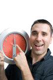 Young Handsome Man Showing Big Clock, Smiling Royalty Free Stock Images