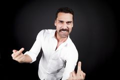 Young handsome man showing fuck off hand gesture. Young handsome man with beard and mustache showing fuck off hand gesture Royalty Free Stock Image