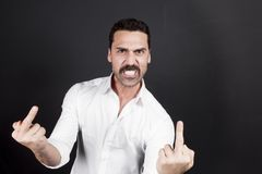 Young handsome man showing fuck off hand gesture. Young handsome man with beard and mustache showing fuck off hand gesture Royalty Free Stock Photography