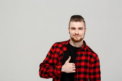 Young handsome man showing okay over grey background. Copy space. Stock Image