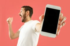 Young handsome man showing smartphone screen isolated on coral background in shock with a surprise face. Young handsome man showing smartphone screen over coral stock photography