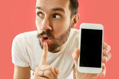 Young handsome man showing smartphone screen isolated on coral background in shock with a surprise face. Young handsome man showing smartphone screen over coral stock images