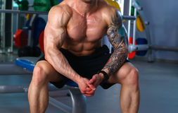Young handsome man sits after workout in the gym Stock Image