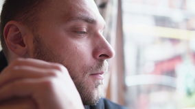 Young handsome man sitting alone at the cafe, waiting and looking out the window. Hands in front of face. Close-up, 4K stock video footage