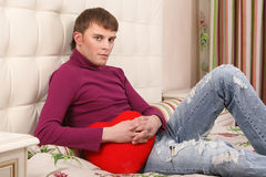 Young handsome man sitting on bed. And holding red heart Stock Image
