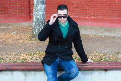 Young Handsome Man Sitting on the Bench in a Black Coat Wearing. Sunglasses Royalty Free Stock Images