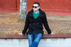 Young Handsome Man Sitting on the Bench in a Black Coat Wearing. Young and Handsome Man Sitting on the Bench in a Black Coat Wearing Sunglasses Royalty Free Stock Photos