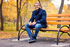 Young handsome man sitting on bench. In park Royalty Free Stock Image