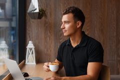Young handsome man sitting in cafe with a cup of coffee. Looking outside the window. Thoughtful confident male having coffee break Royalty Free Stock Image