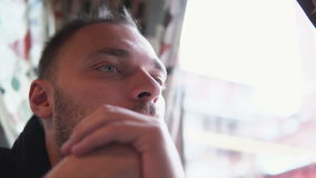 Young handsome man sitting in cafe near window and look into distance. Holding hands in front of face. Close-up, 4K stock video
