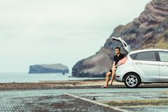 Young handsome man sitting in car trunk and enjoy beauty view of rocks and ocean. Car trip. Summer travel. stock photos