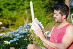 Young handsome man sitting on chair and reading book Stock Photography
