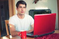 Young handsome man sitting with coffee and laptop Royalty Free Stock Photography