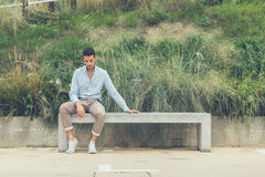 Young handsome man sitting on a concrete bench Stock Images