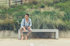 Young handsome man sitting on a concrete bench Royalty Free Stock Photography