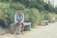 Young handsome man sitting on a concrete bench Stock Image